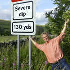 Rick Steves next to a Severe Dip road sign